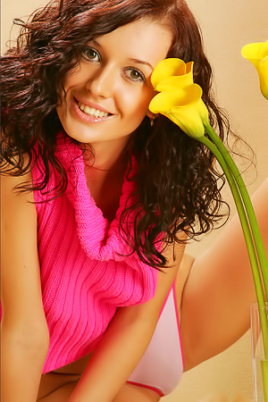 Curly brunette is posing with flowers