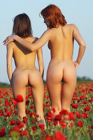 Two women are posing in a field of flowers