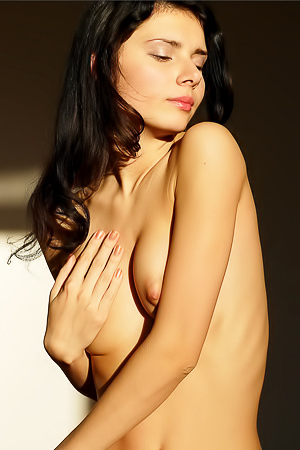 Naked cutie caresses body with silk sheet.